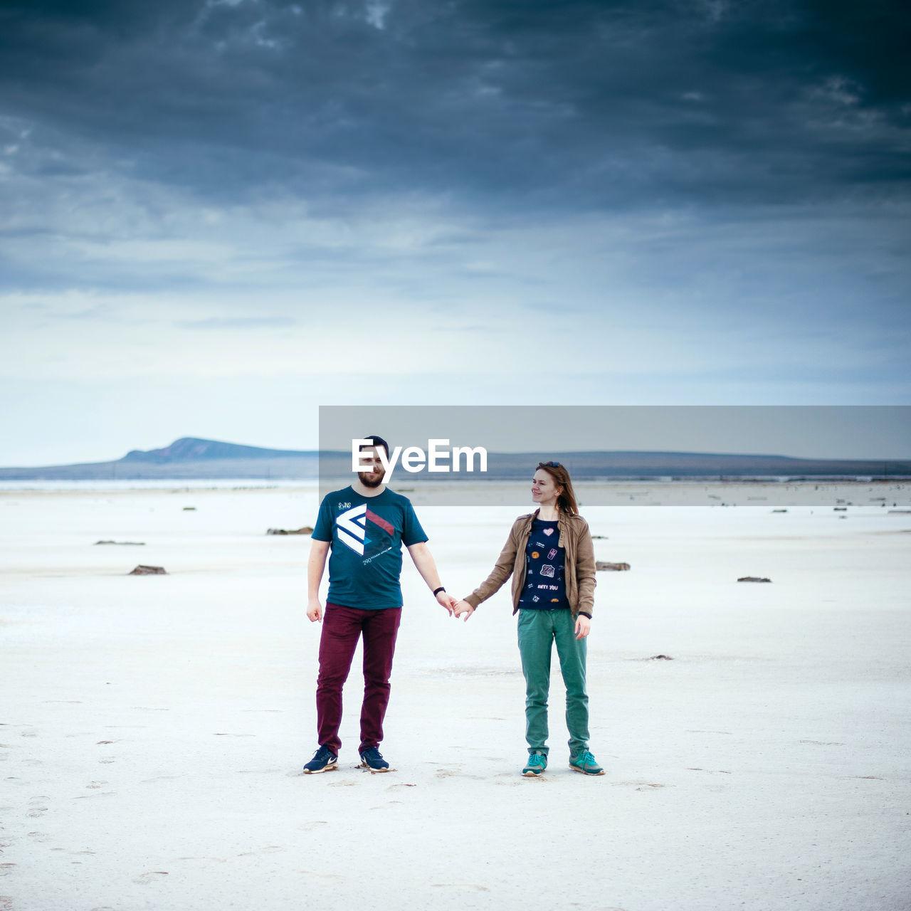 Couple enjoying at beach against cloudy sky