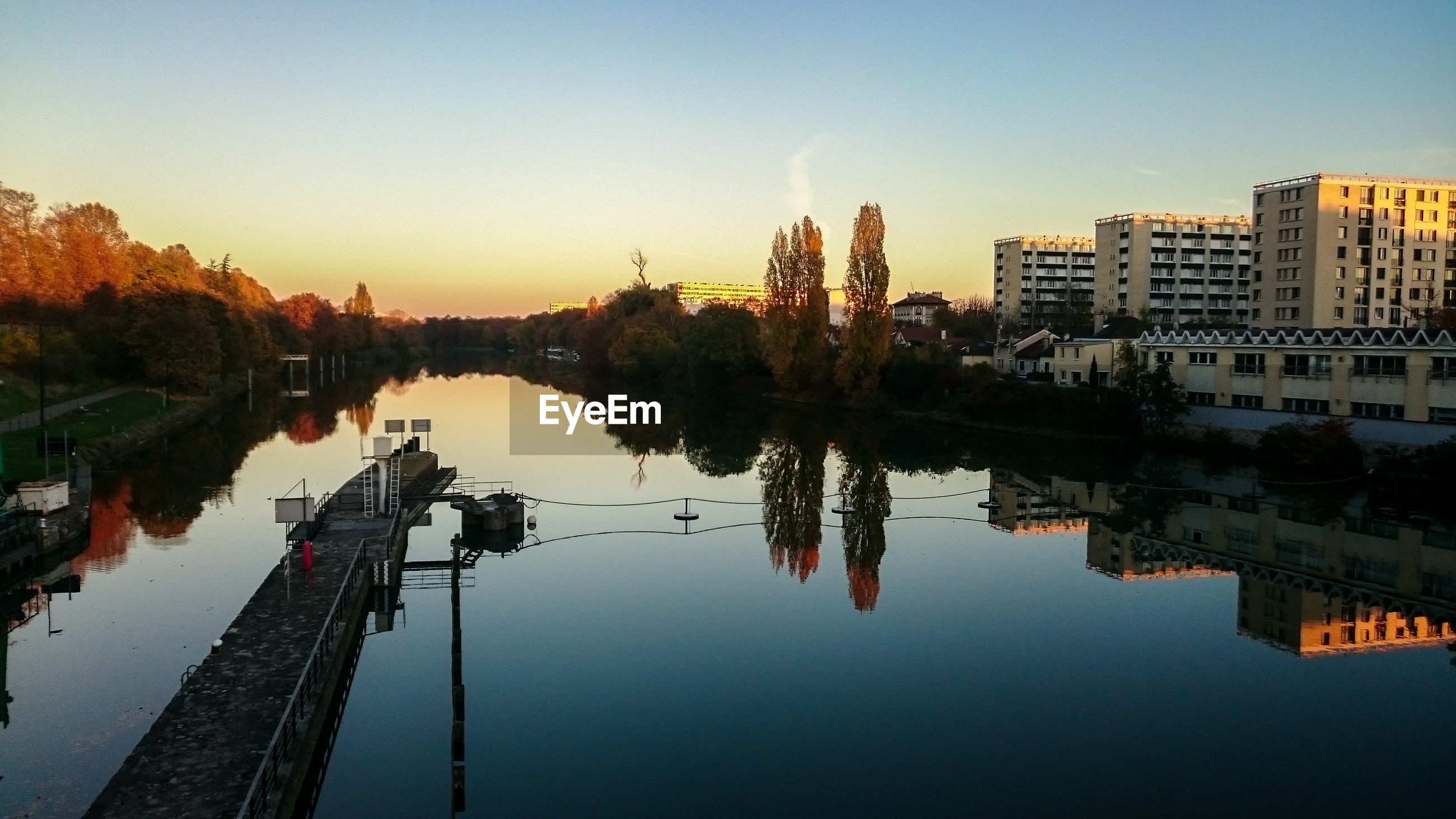 River by city against sky during sunset