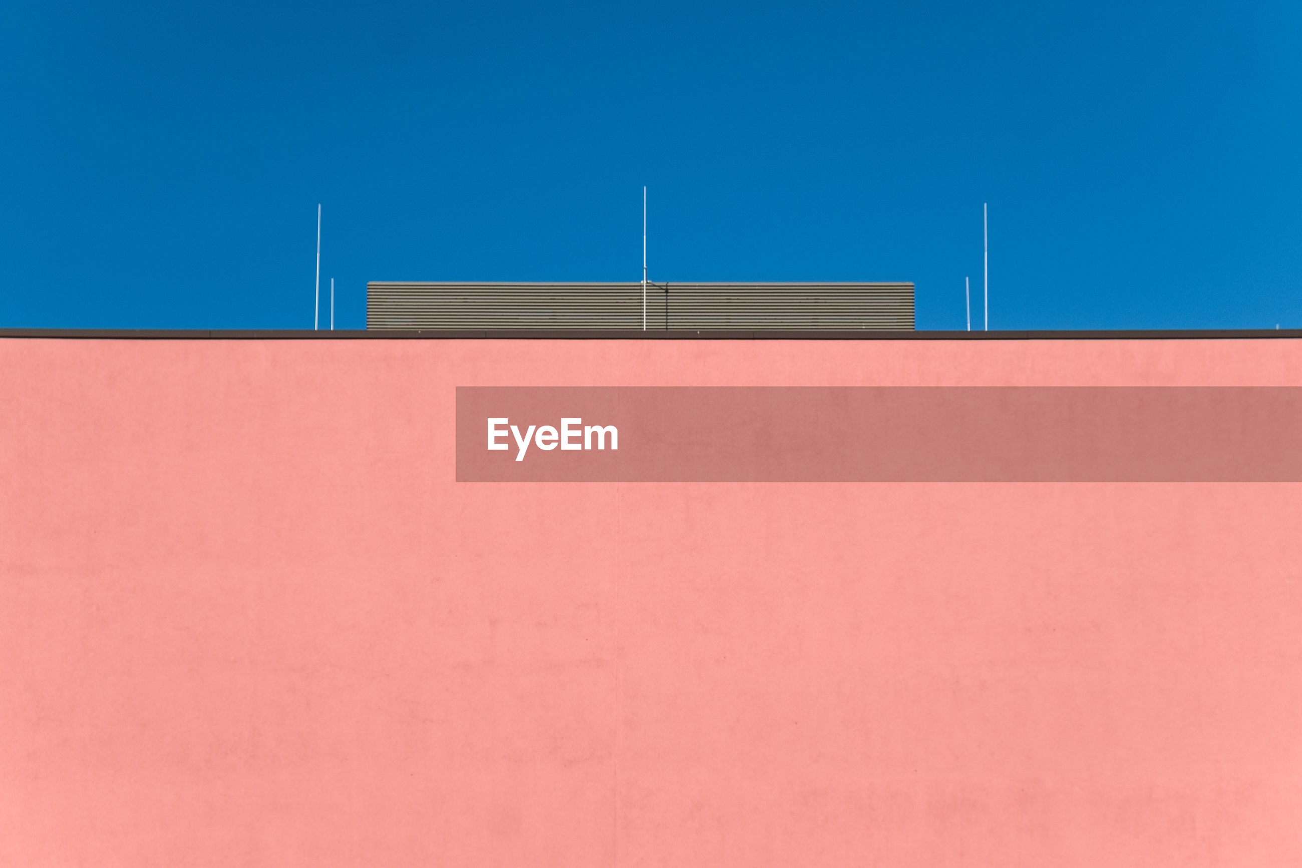 Low angle view of orange wall against blue sky