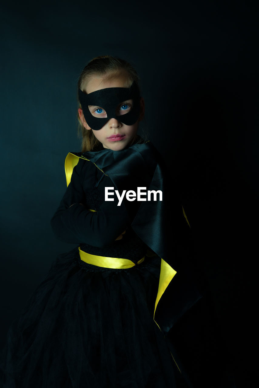 Portrait Of Girl Wearing Costume Standing Against Black Background
