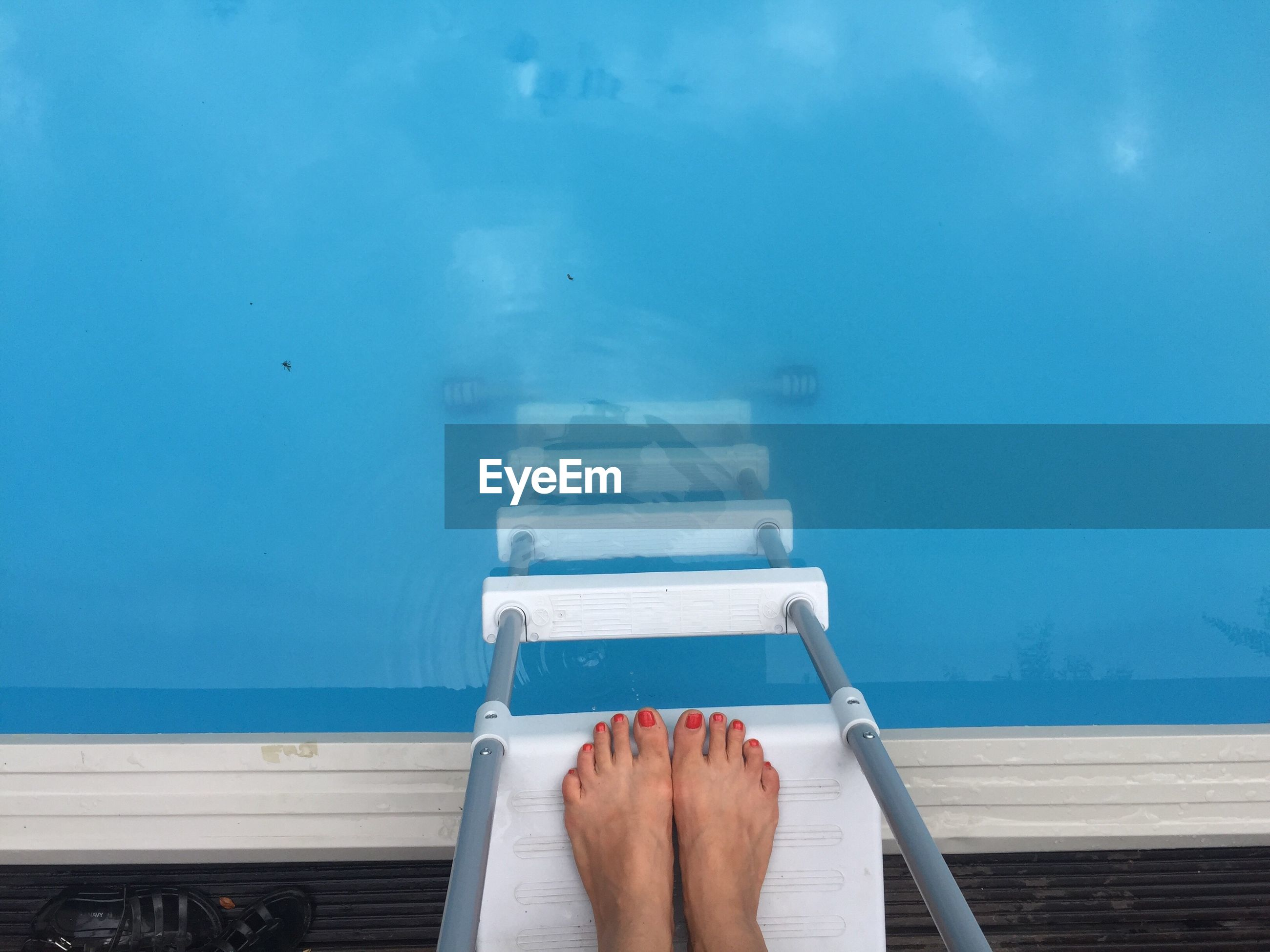 Low section of woman standing on ladder at swimming pool