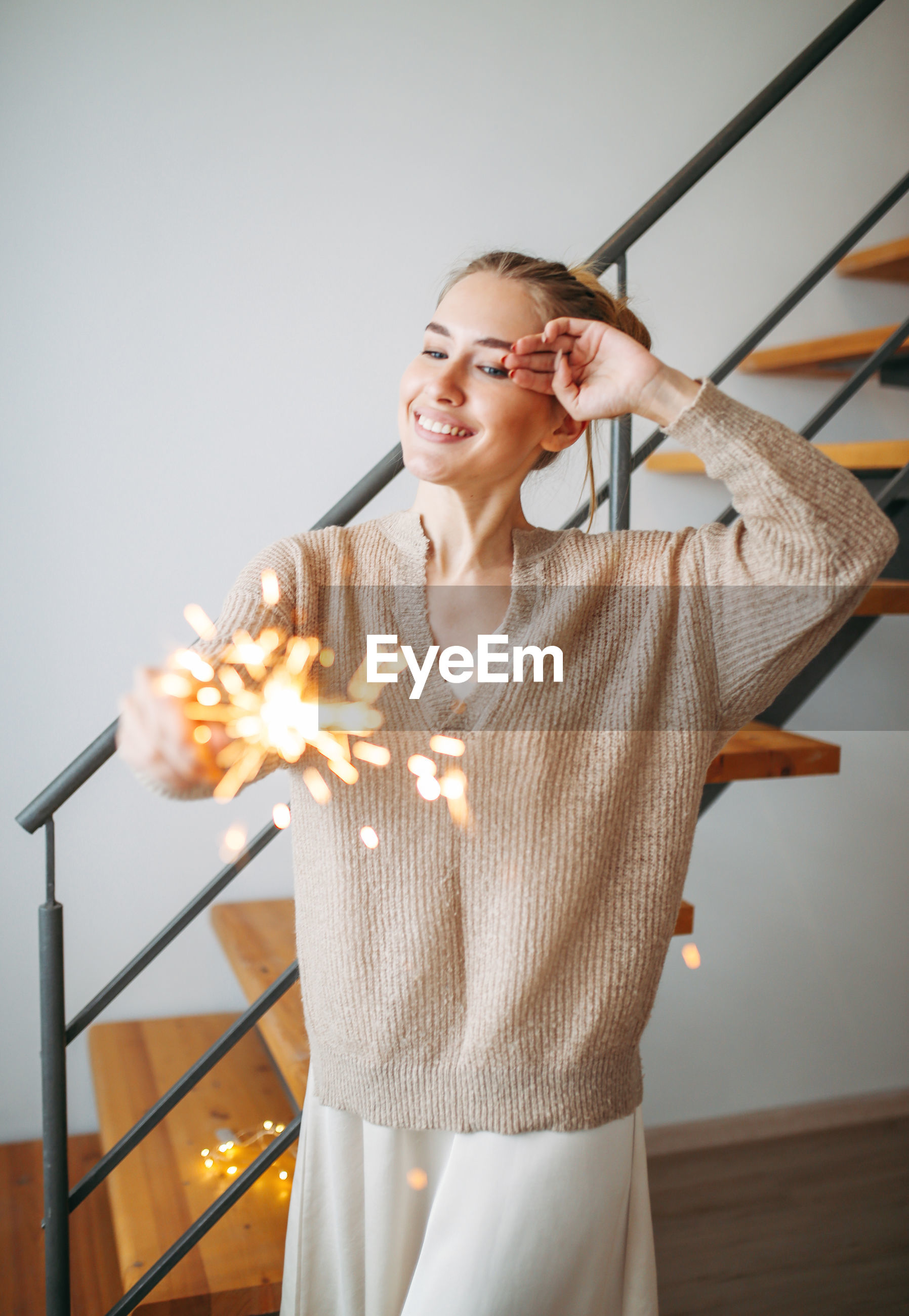 Smiling young woman holding sparkler at home