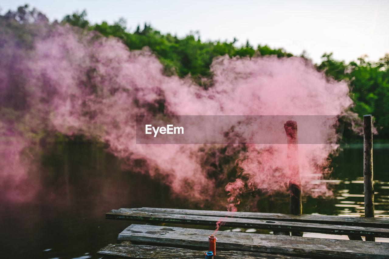 Close-up of pink smoke against lake