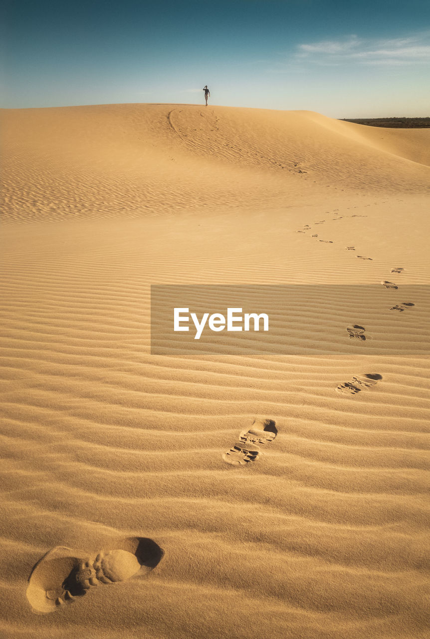 Scenic view of sandy desert with footprints of person walking