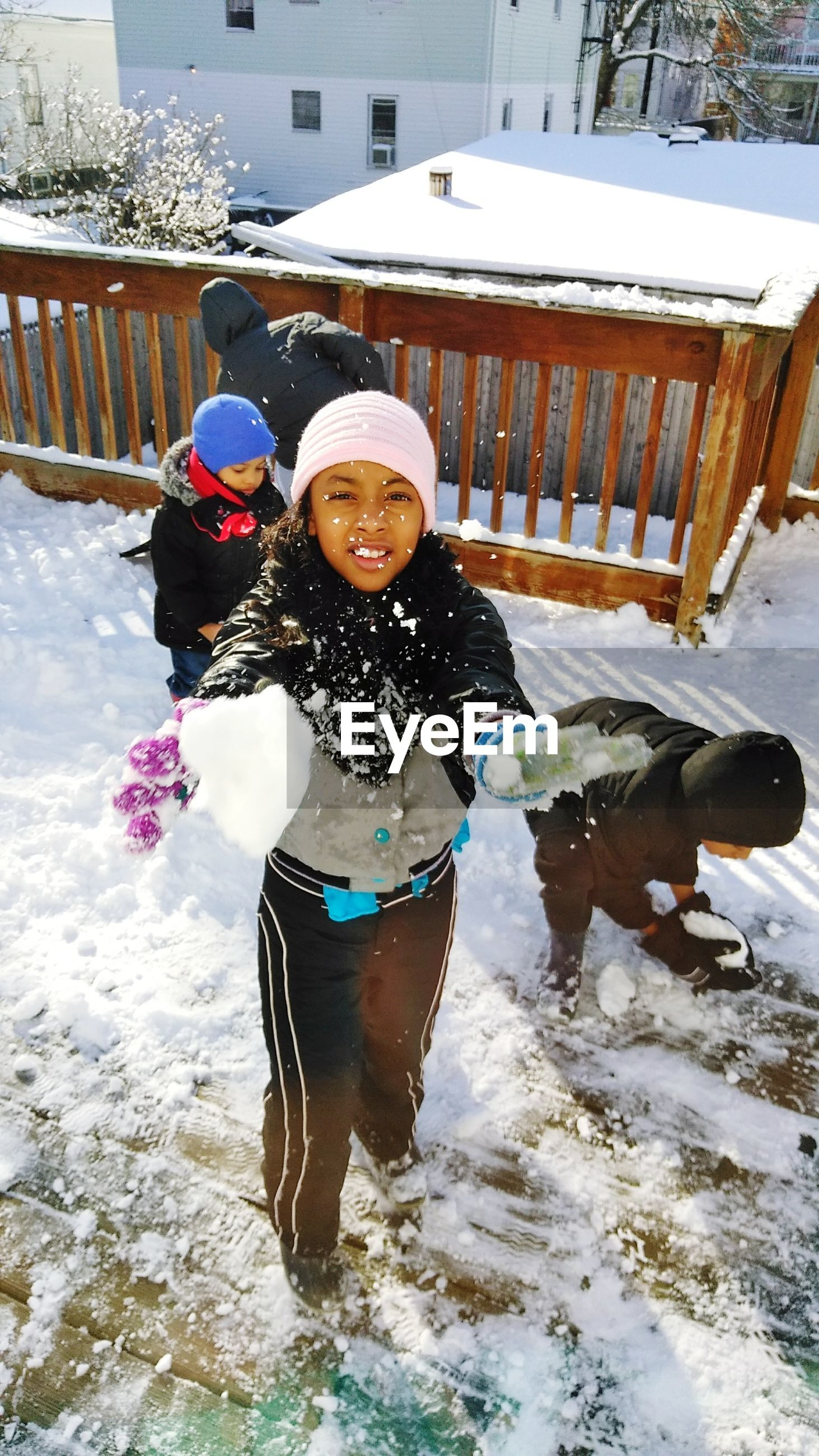 Siblings playing with snow during winter