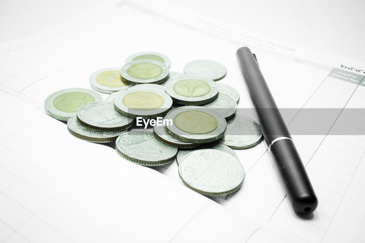 High angle view of coins with pen and paper over white background
