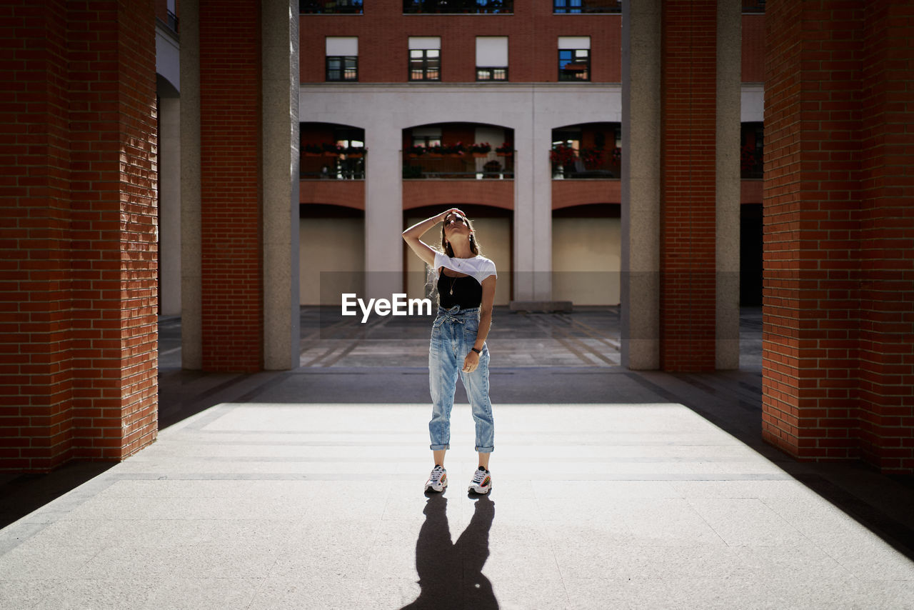 FULL LENGTH OF YOUNG WOMAN STANDING AT BUILDING