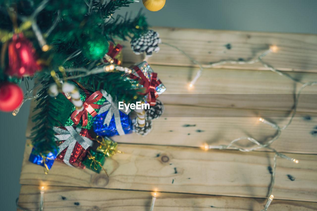 High angle view of christmas presents and tree on table at home