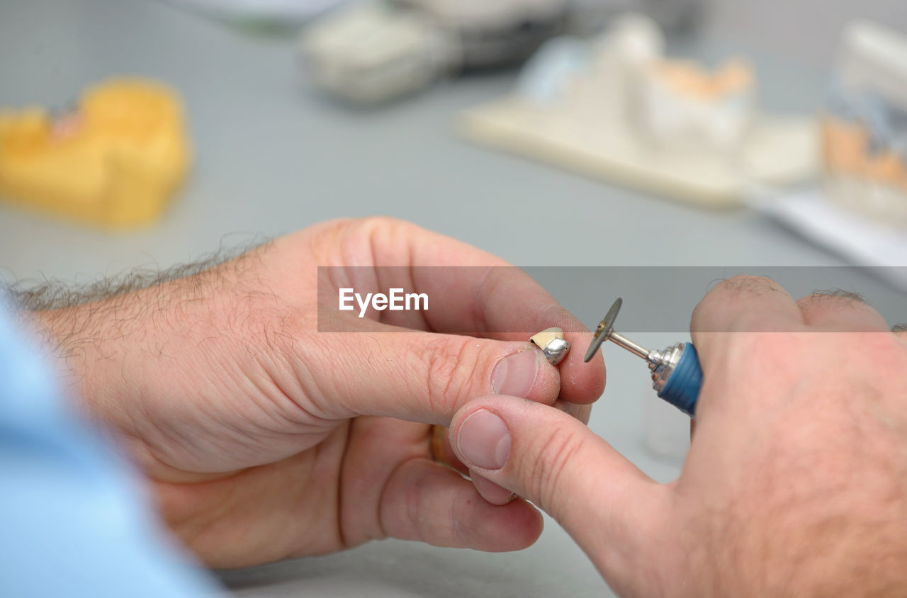 Cropped hands of male dental technician working in laboratory