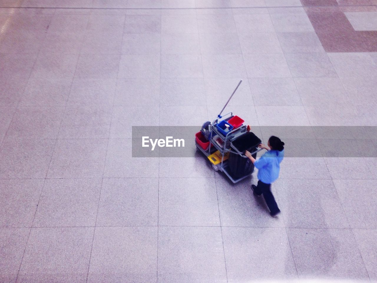 High angle view of female caretaker pushing cart at airport