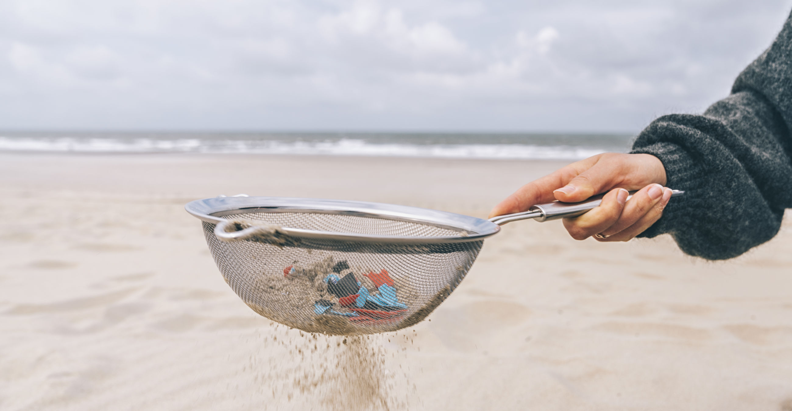 Cropped hand of woman holding colander on beach