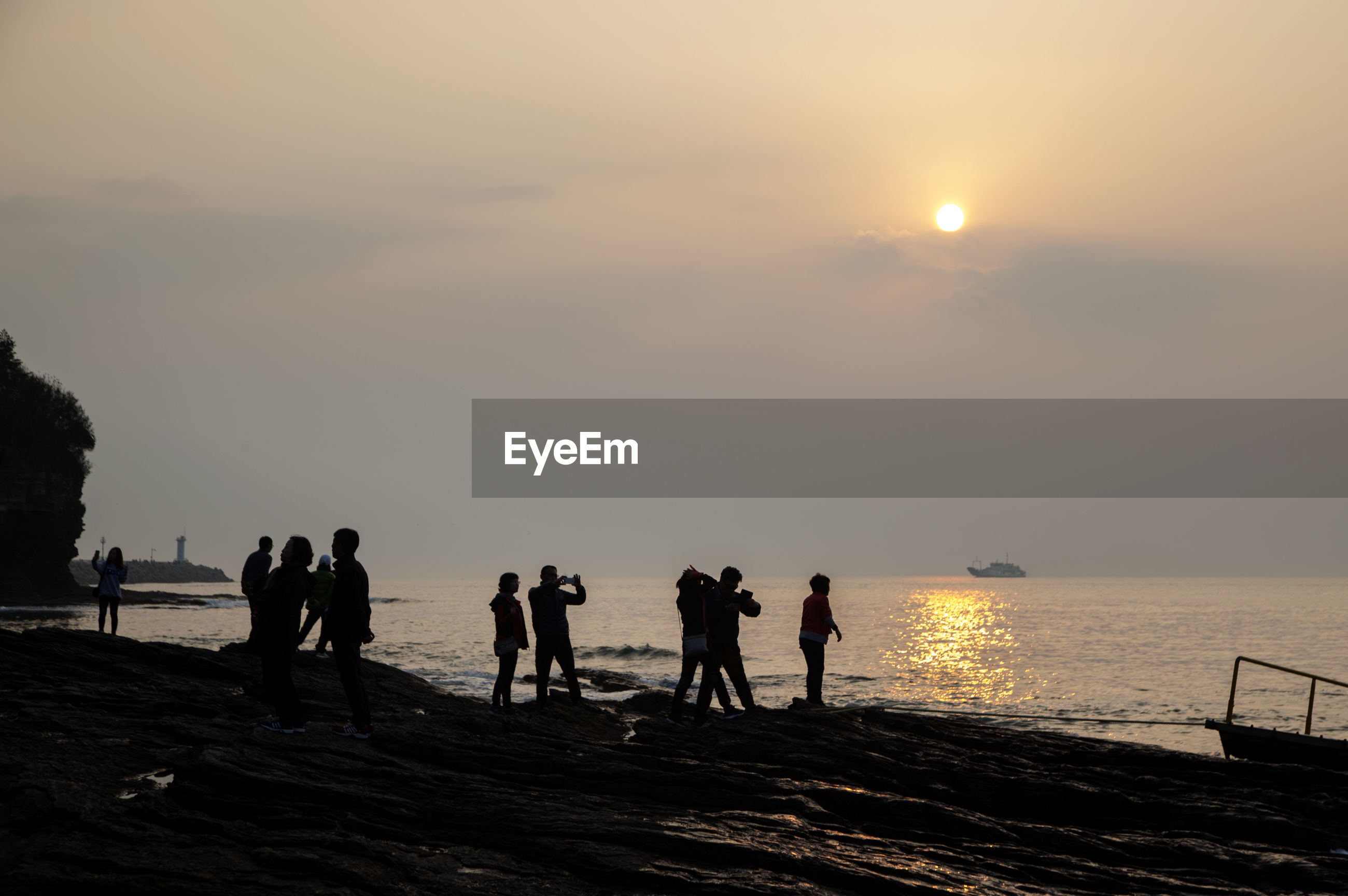 Silhouette people standing on chaeseokgang cliffs during sunset