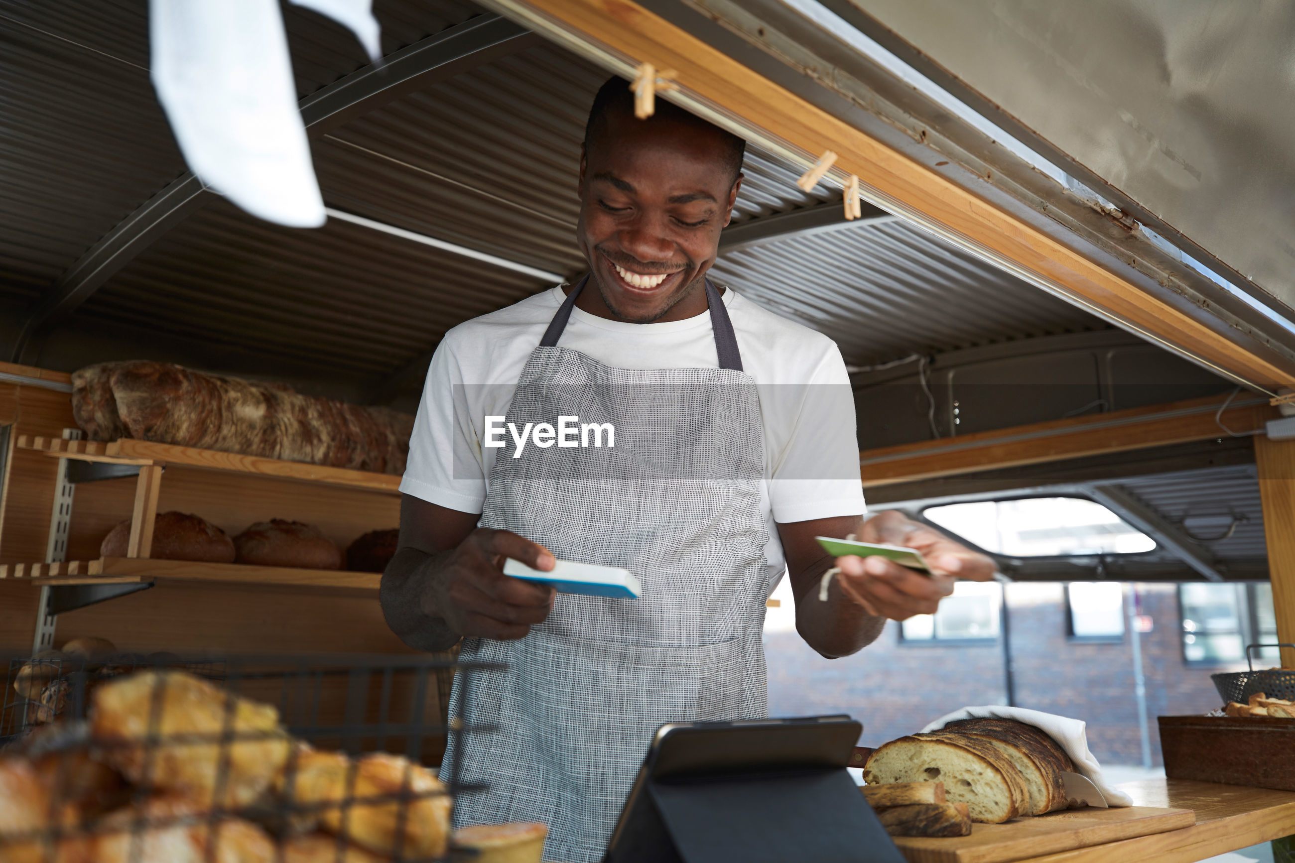 Smiling salesman holding credit card and reader in food truck