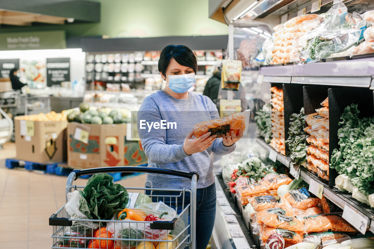 Grocery shopping. middle age woman with short dark hair in protective face mask choosing buying food