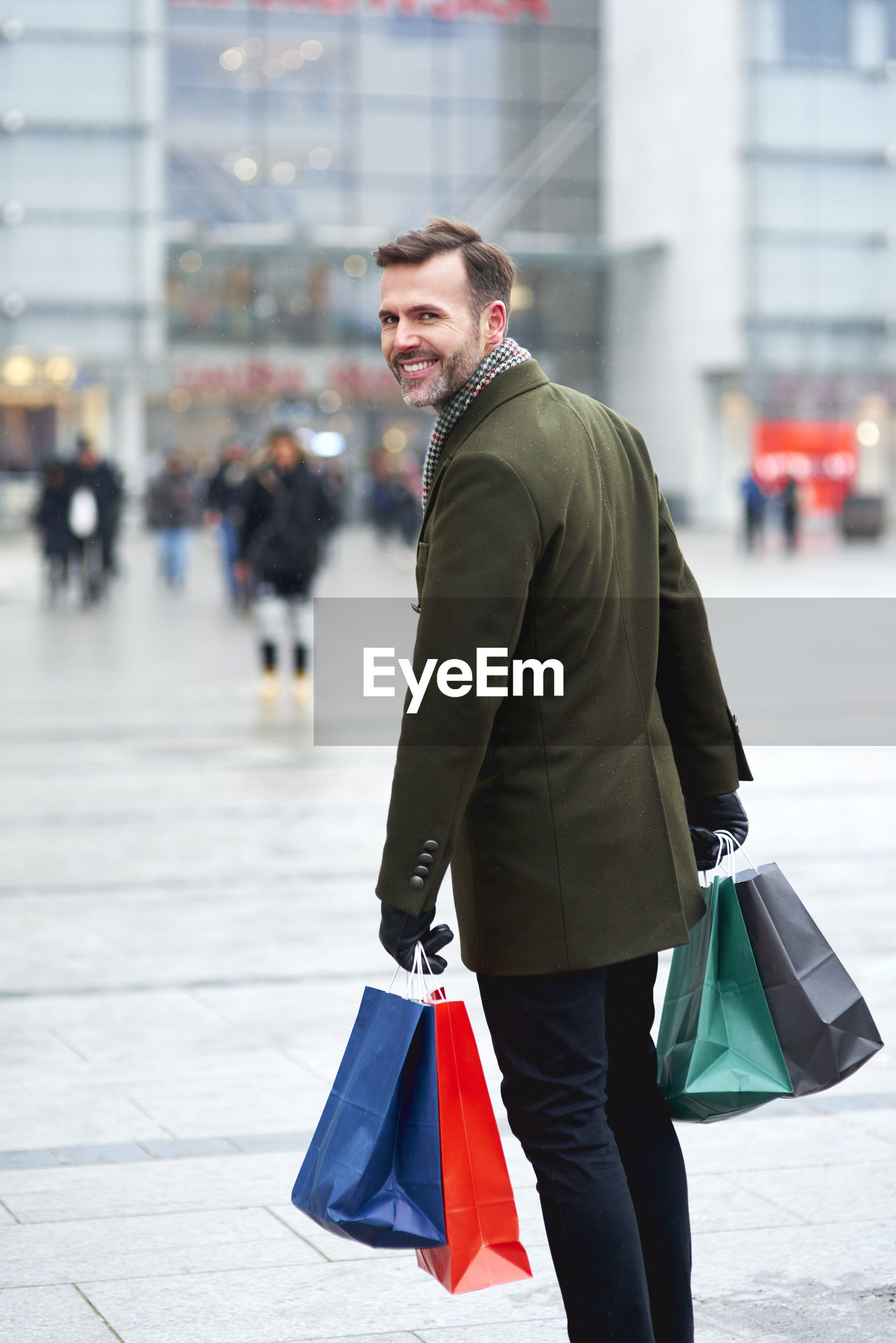Portrait of man holding shopping bags while standing in city during winter