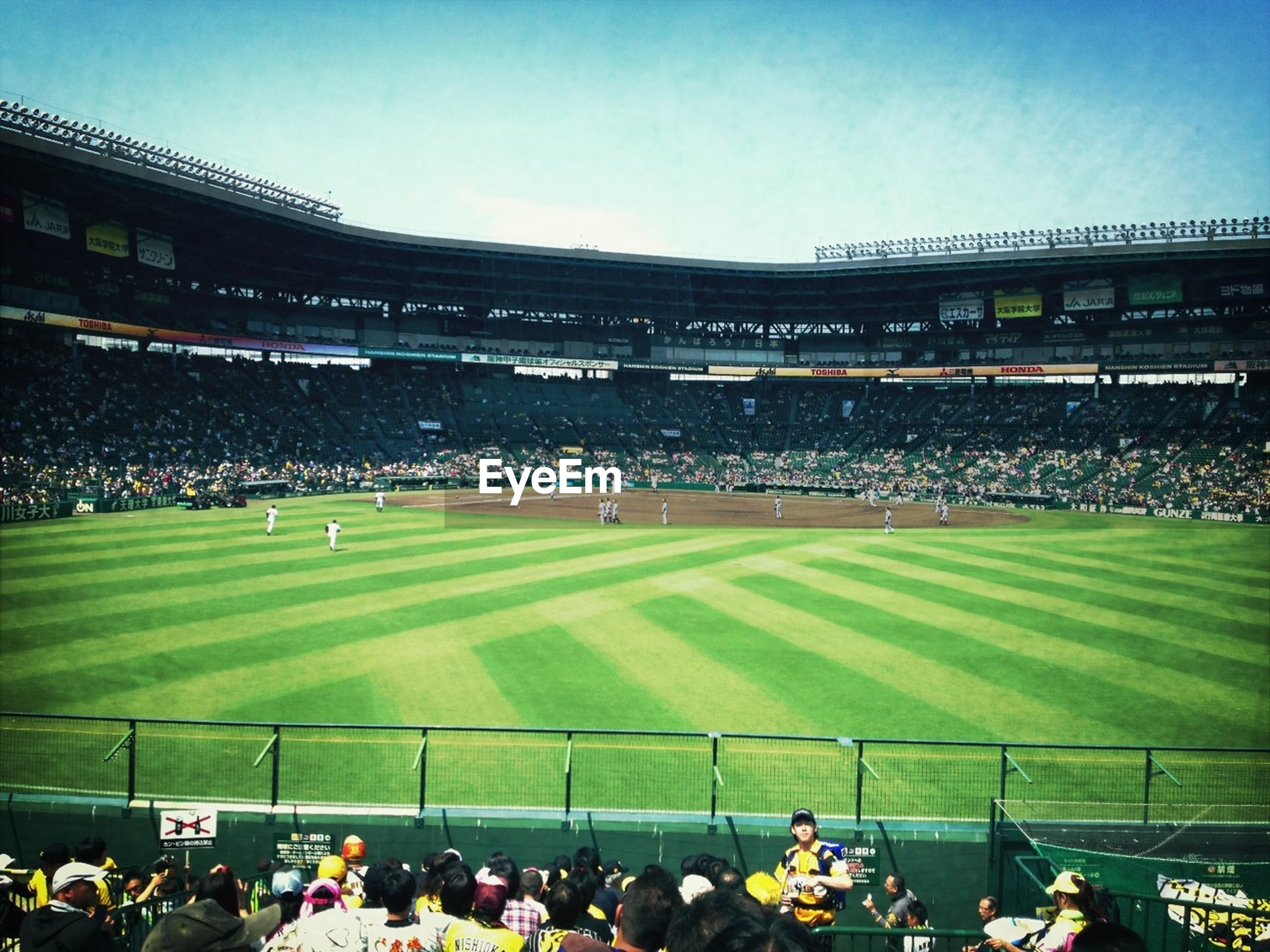 large group of people, crowd, men, person, lifestyles, leisure activity, built structure, architecture, building exterior, mixed age range, stadium, green color, sky, spectator, field, grass, high angle view, clear sky, outdoors