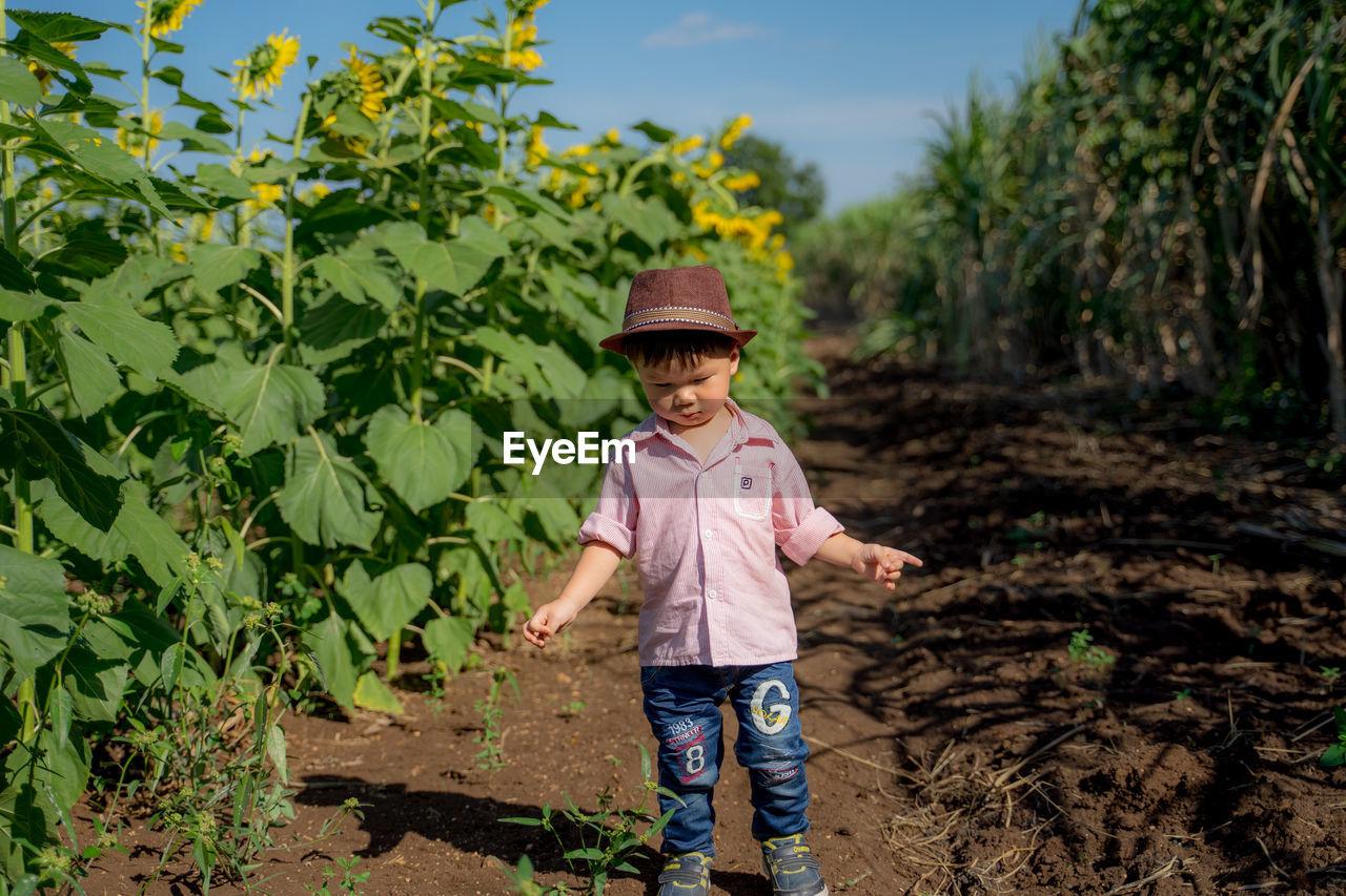 Cute smiling baby boy in hat standing on field
