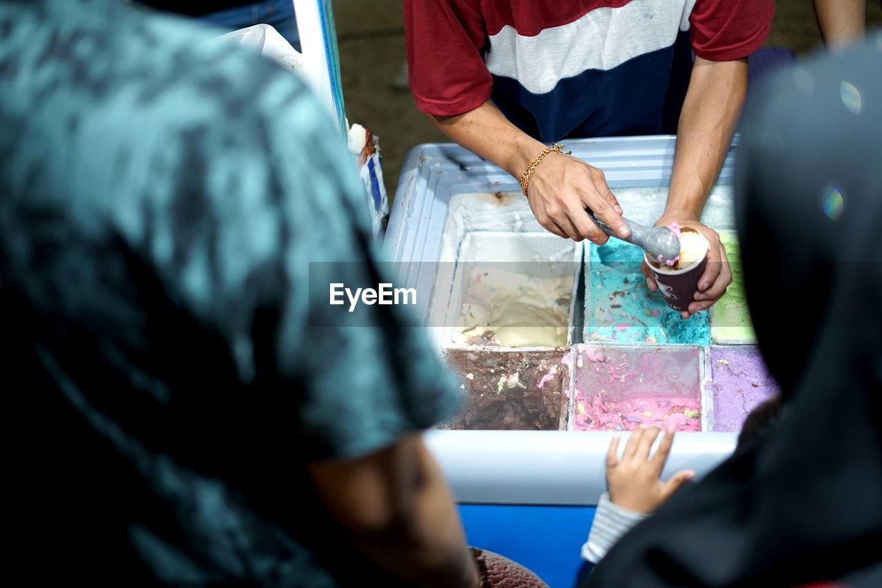 Vendor prepare colourful ice cream at street food bazaar