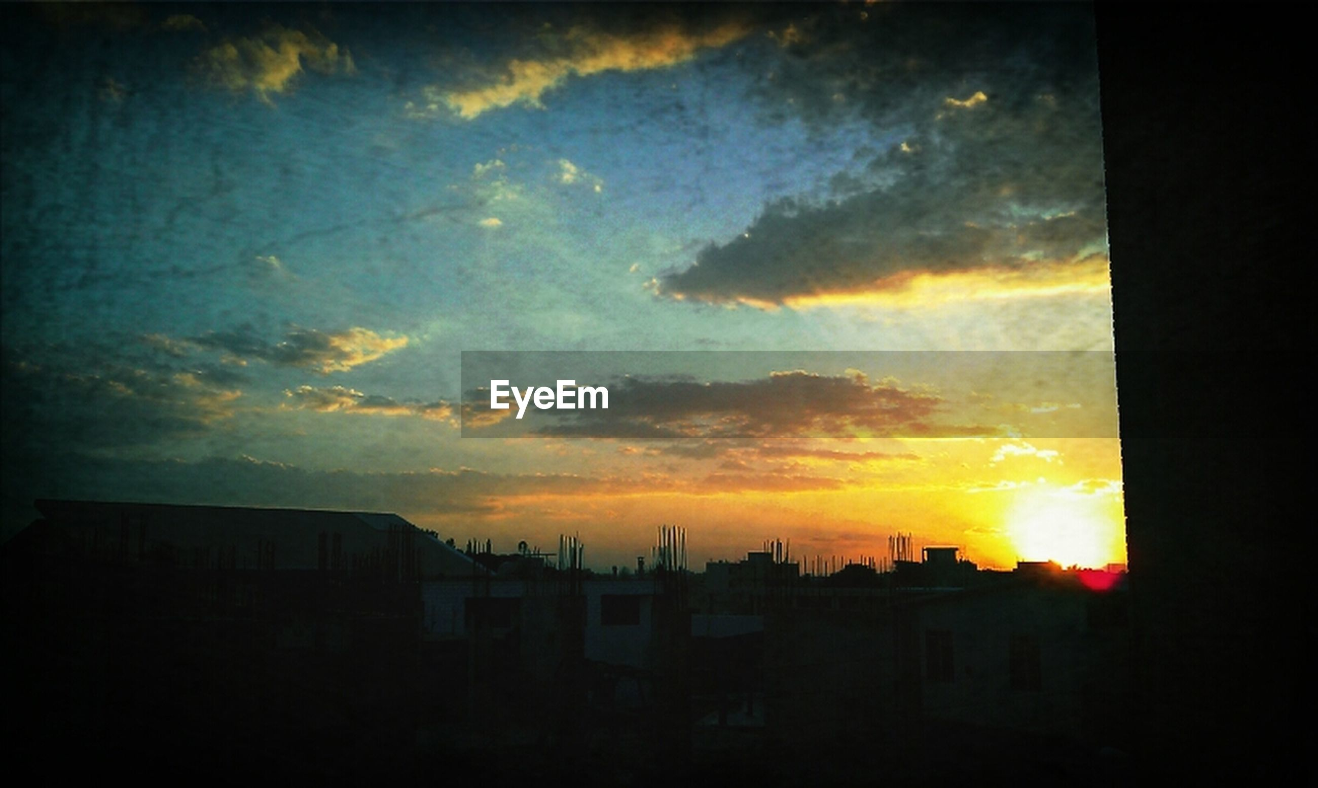 sunset, sky, building exterior, architecture, silhouette, built structure, orange color, cloud - sky, dramatic sky, cloudy, house, beauty in nature, cloud, scenics, low angle view, nature, sun, dark, residential structure, outdoors