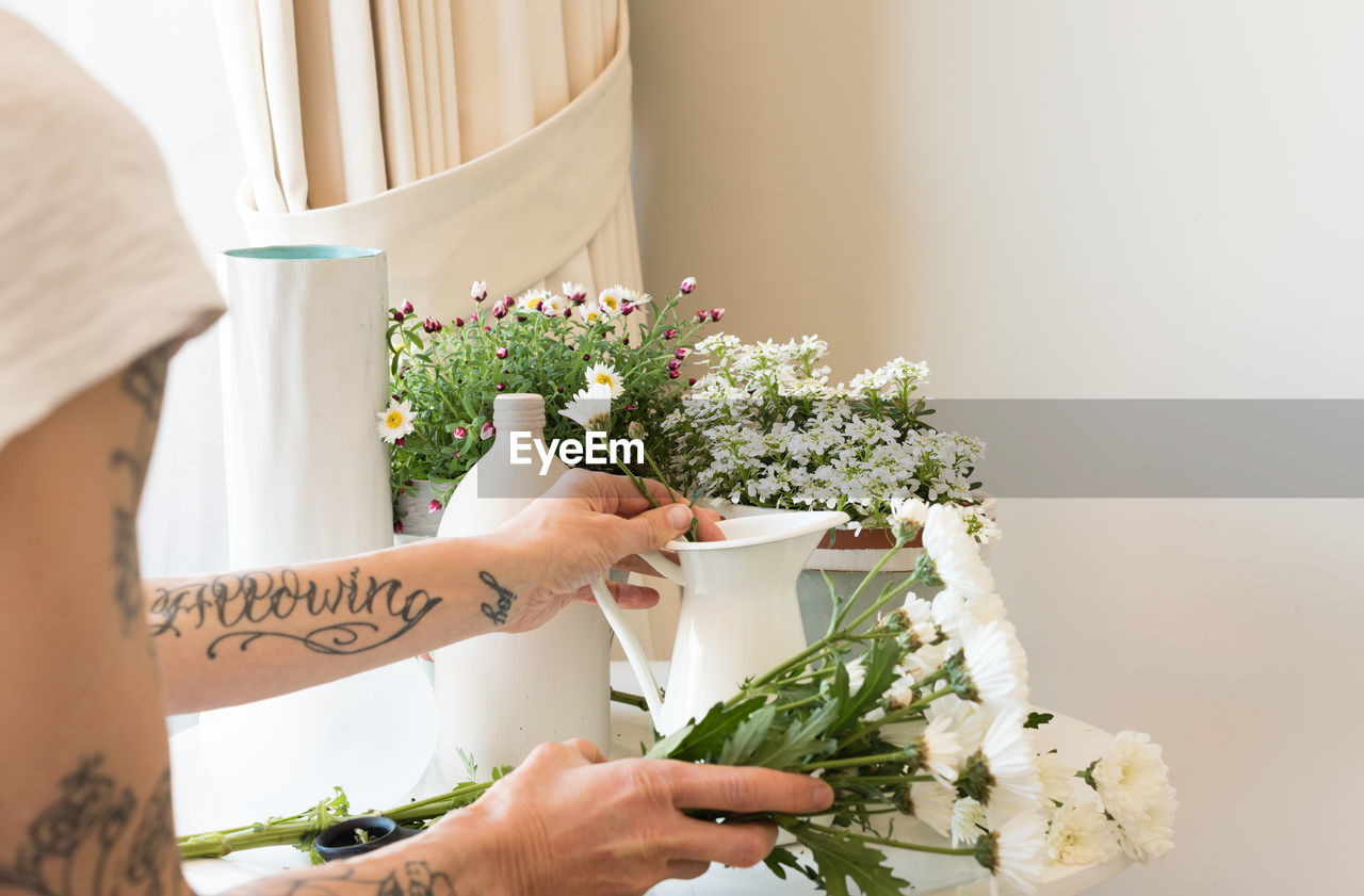 Cropped Hands Of Mature Woman Arranging Flowers In Vase