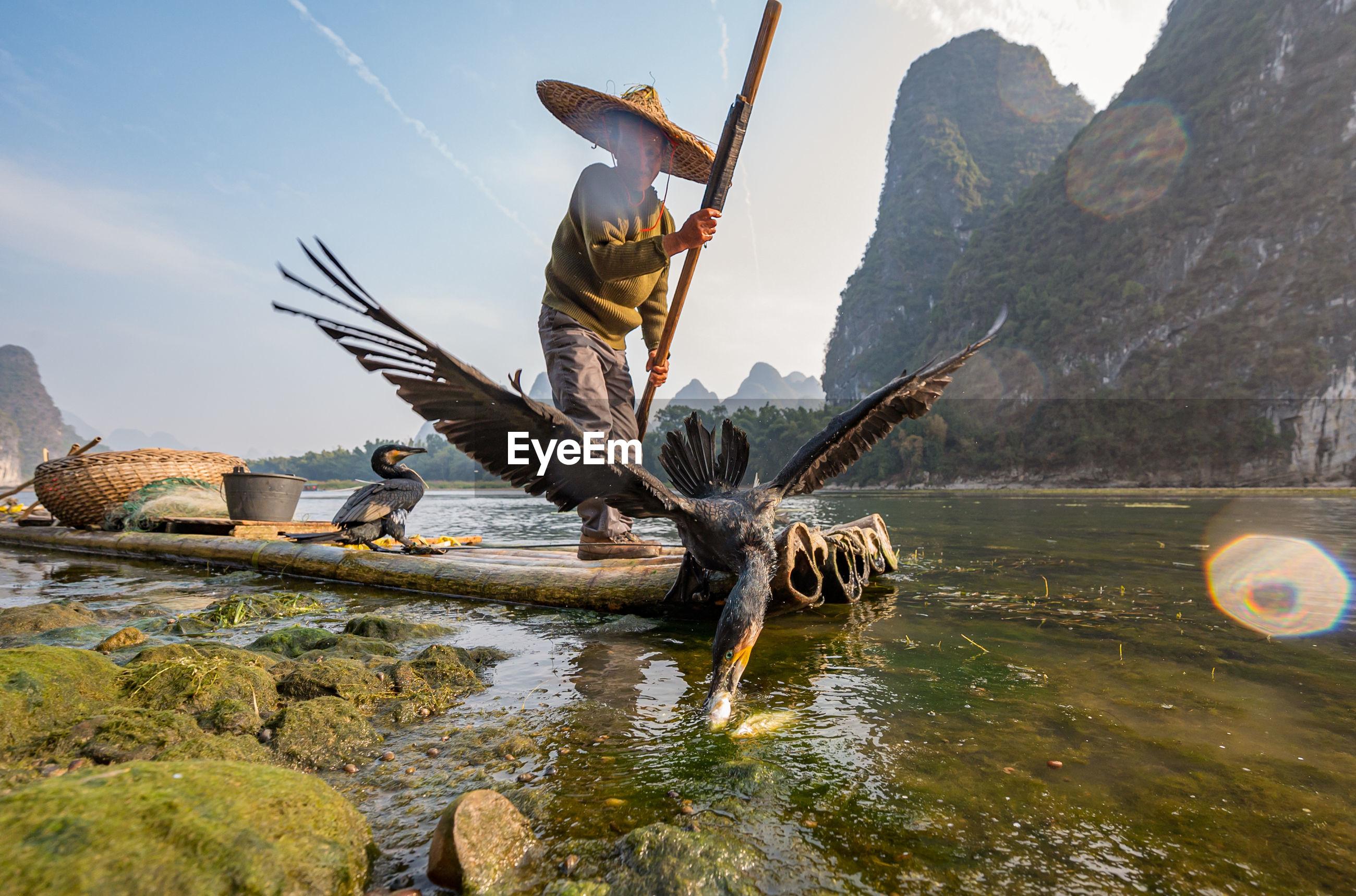 Man standing on wooden raft fishing in lake