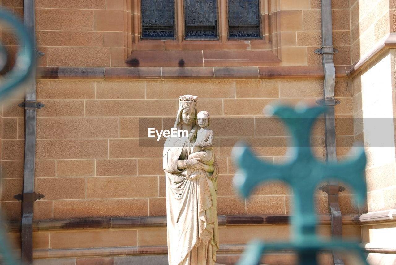 statue, human representation, sculpture, male likeness, art and craft, female likeness, built structure, building exterior, architecture, day, low angle view, outdoors, no people