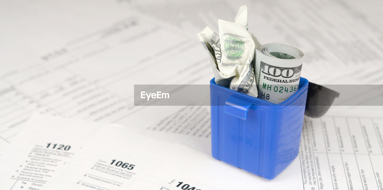 finance, paper, indoors, table, wealth, business, currency, blue, paper currency, close-up, high angle view, number, still life, focus on foreground, selective focus, no people, pen, text, education, container, expense