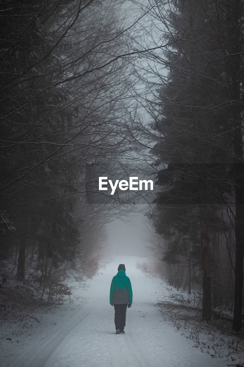 Young girl in a green winter jacket walks in the ugly, foggy and cold weather in beskydy moutains