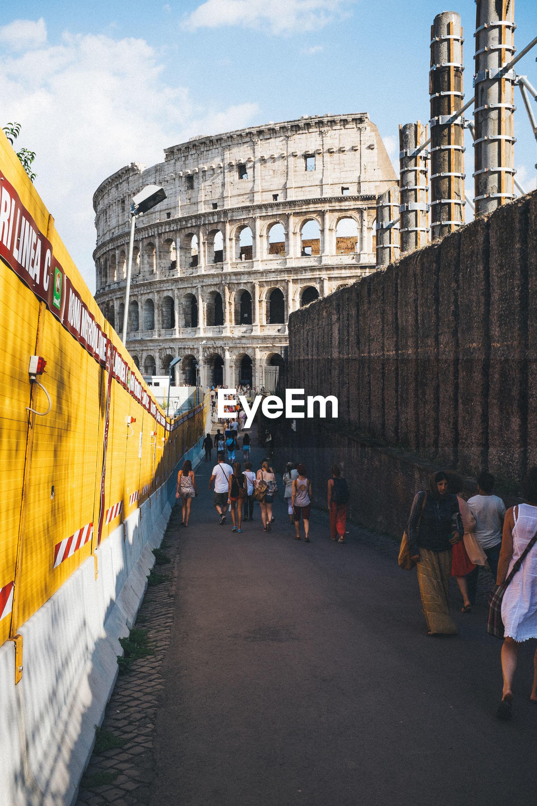 Tourists walking towards coliseum