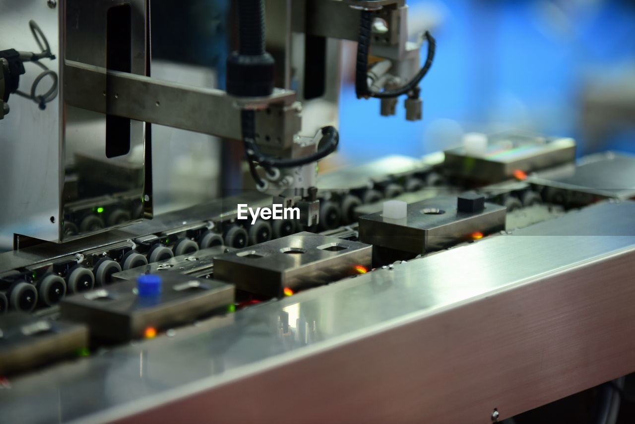 equipment, technology, selective focus, close-up, machinery, indoors, industry, no people, factory, electronics industry, metal, control, manufacturing equipment, machine part, focus on foreground, electrical equipment, still life, computer part, computer chip, sewing machine