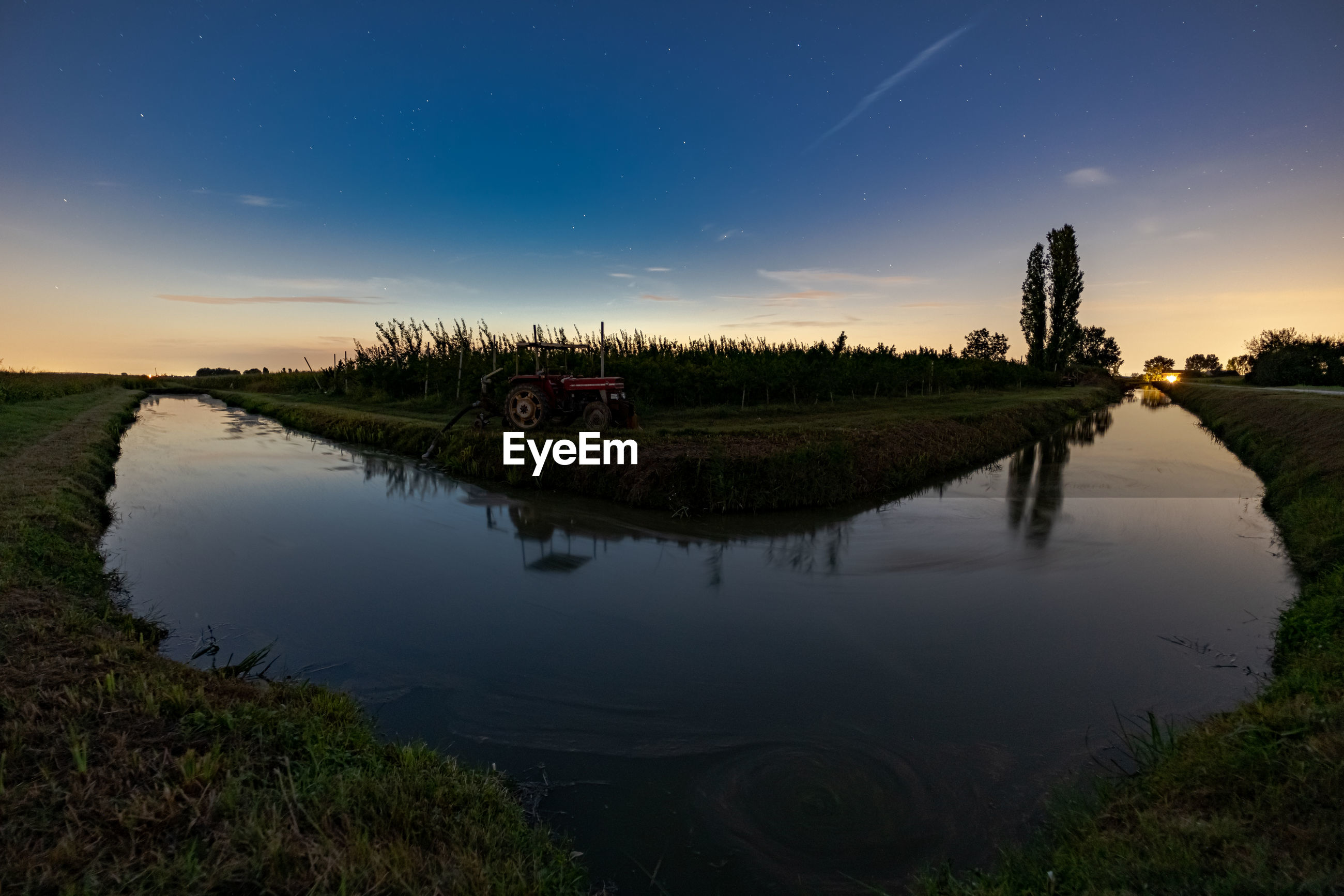 Scenic view of a little river against sky at sunset