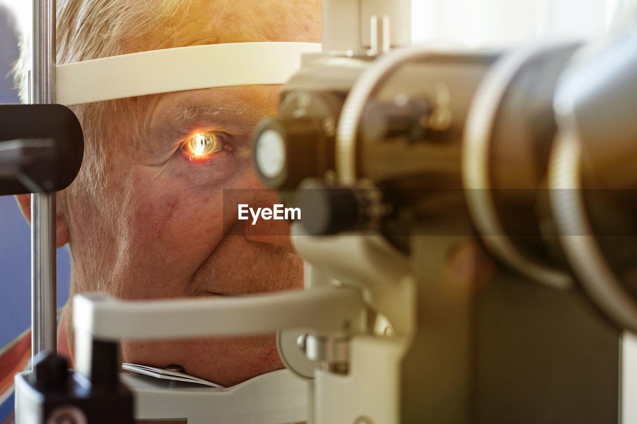 Close-up of man checking eyes