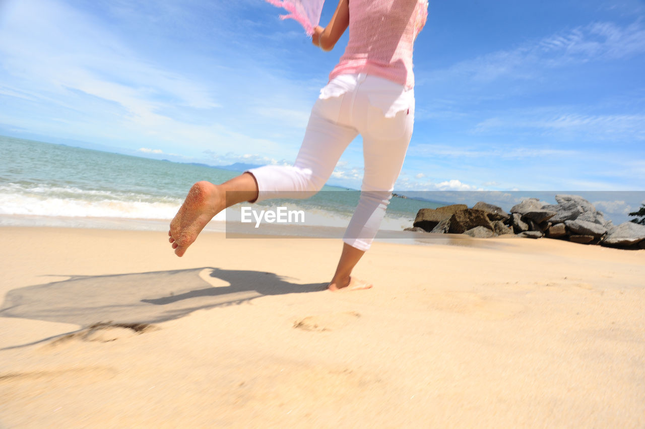 Low section of woman running on sand against sea at beach