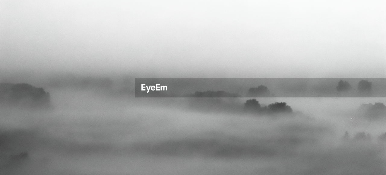 AERIAL VIEW OF FOG ON LANDSCAPE AGAINST SKY