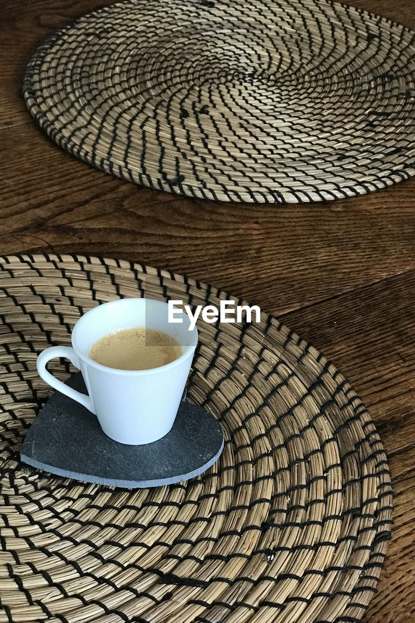 cup, mug, coffee, still life, drink, coffee cup, coffee - drink, refreshment, table, food and drink, indoors, high angle view, no people, hat, place mat, pattern, crockery, close-up, freshness, clothing, non-alcoholic beverage, tea cup