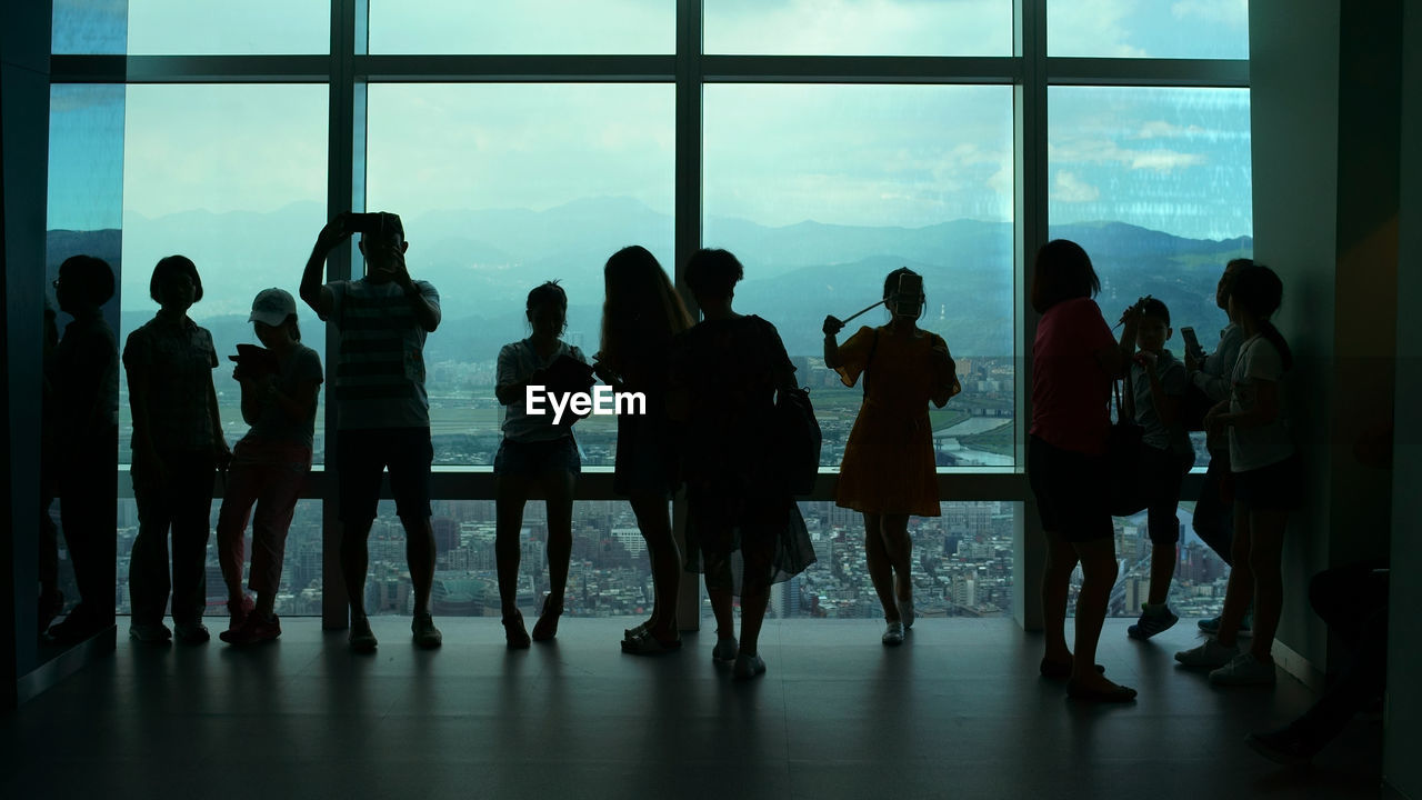 window, indoors, men, real people, medium group of people, standing, full length, women, togetherness, silhouette, day, lifestyles, sky, people
