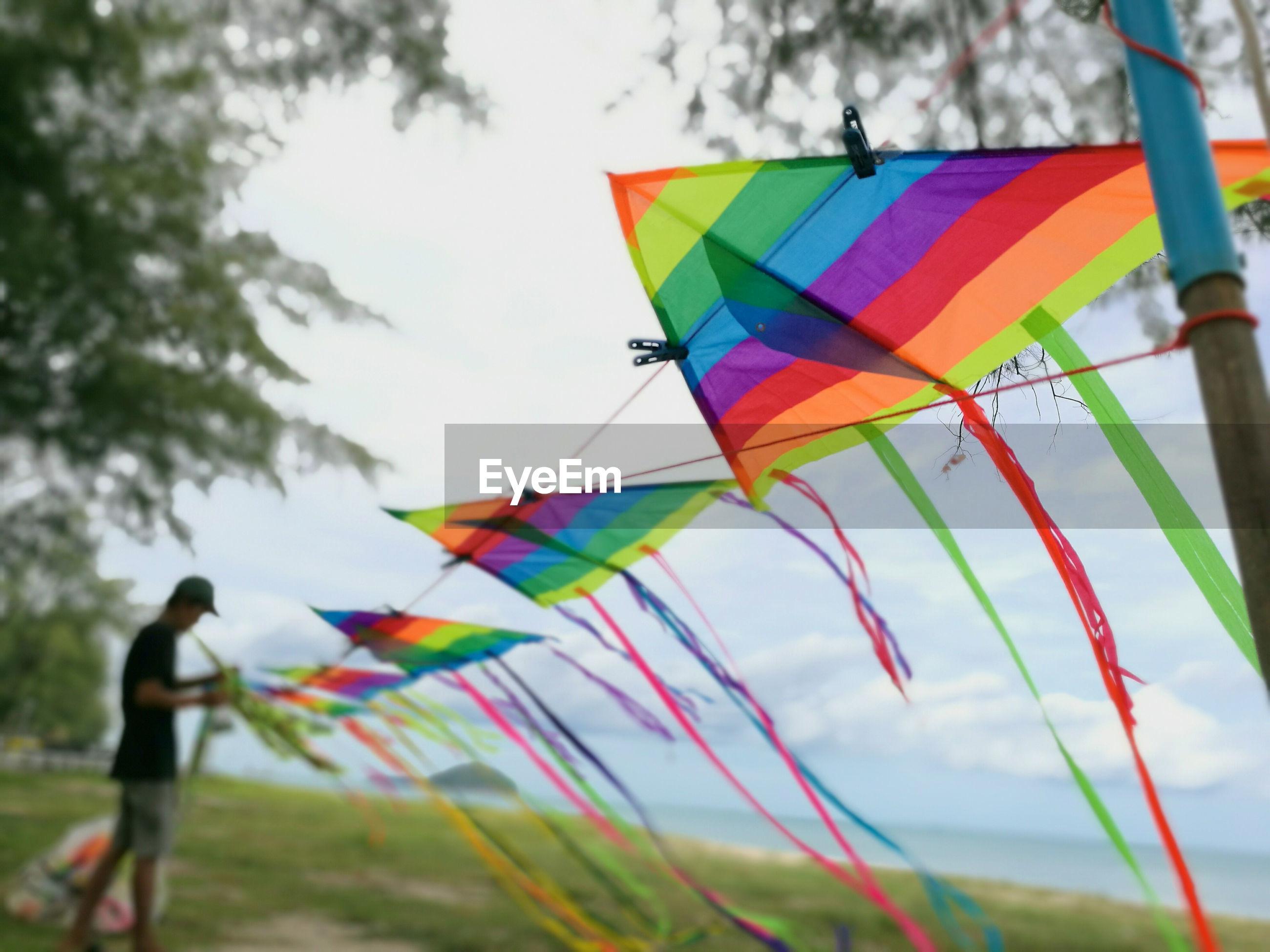Colorful kites on clothesline against sky