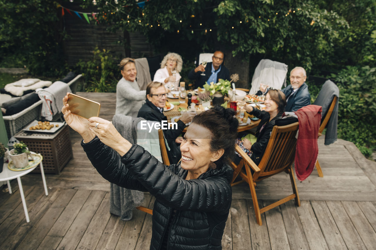 GROUP OF PEOPLE SITTING ON TABLE AT SIDEWALK