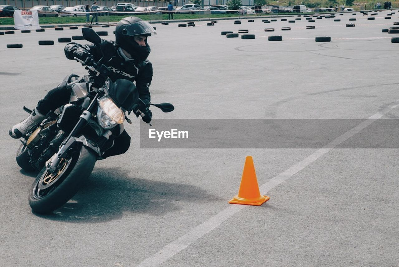 helmet, protection, safety, headwear, sports helmet, men, real people, one person, sport, transportation, riding, motorcycle, full length, outdoors, day, uniform, competition, road, lifestyles, protective workwear, traffic cone, sports uniform, one man only, adult, people