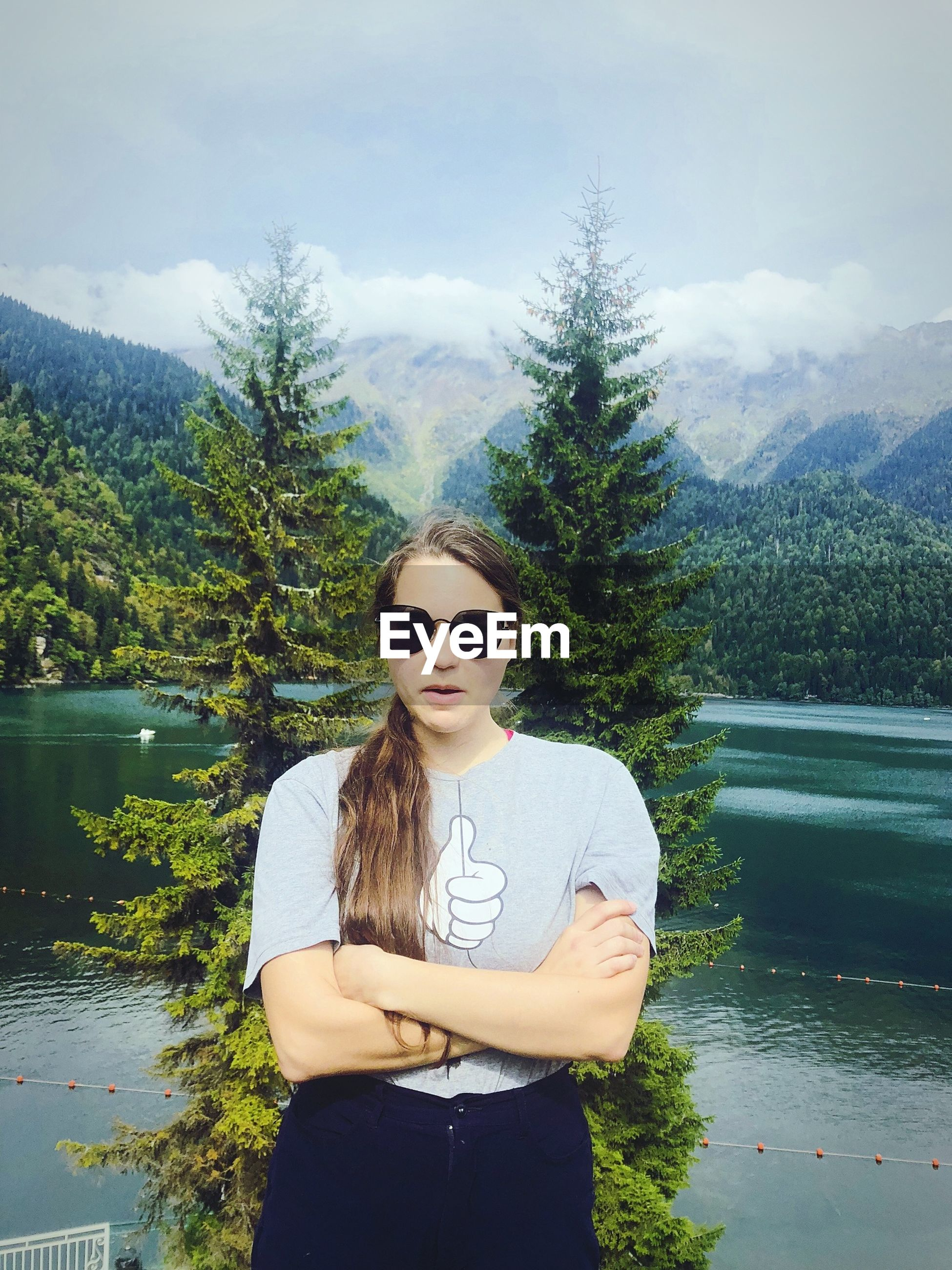 Young woman wearing sunglasses while standing by lake against sky