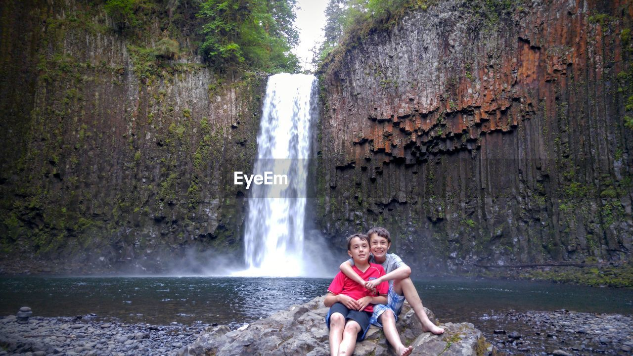 Portrait Of Brothers Sitting On Rock Against Waterfall