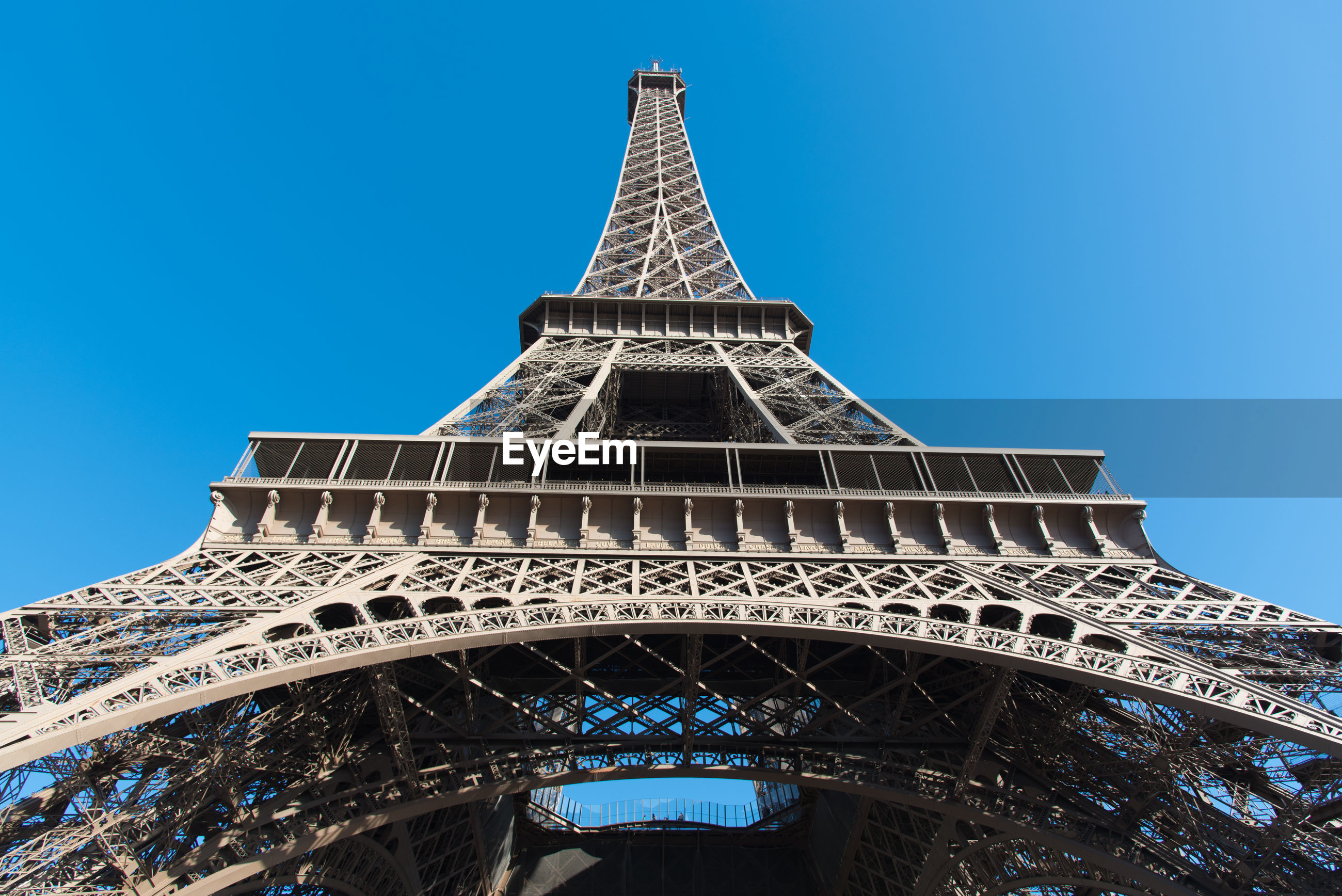 Low angle view of eiffel tower against clear blue sky during sunny day