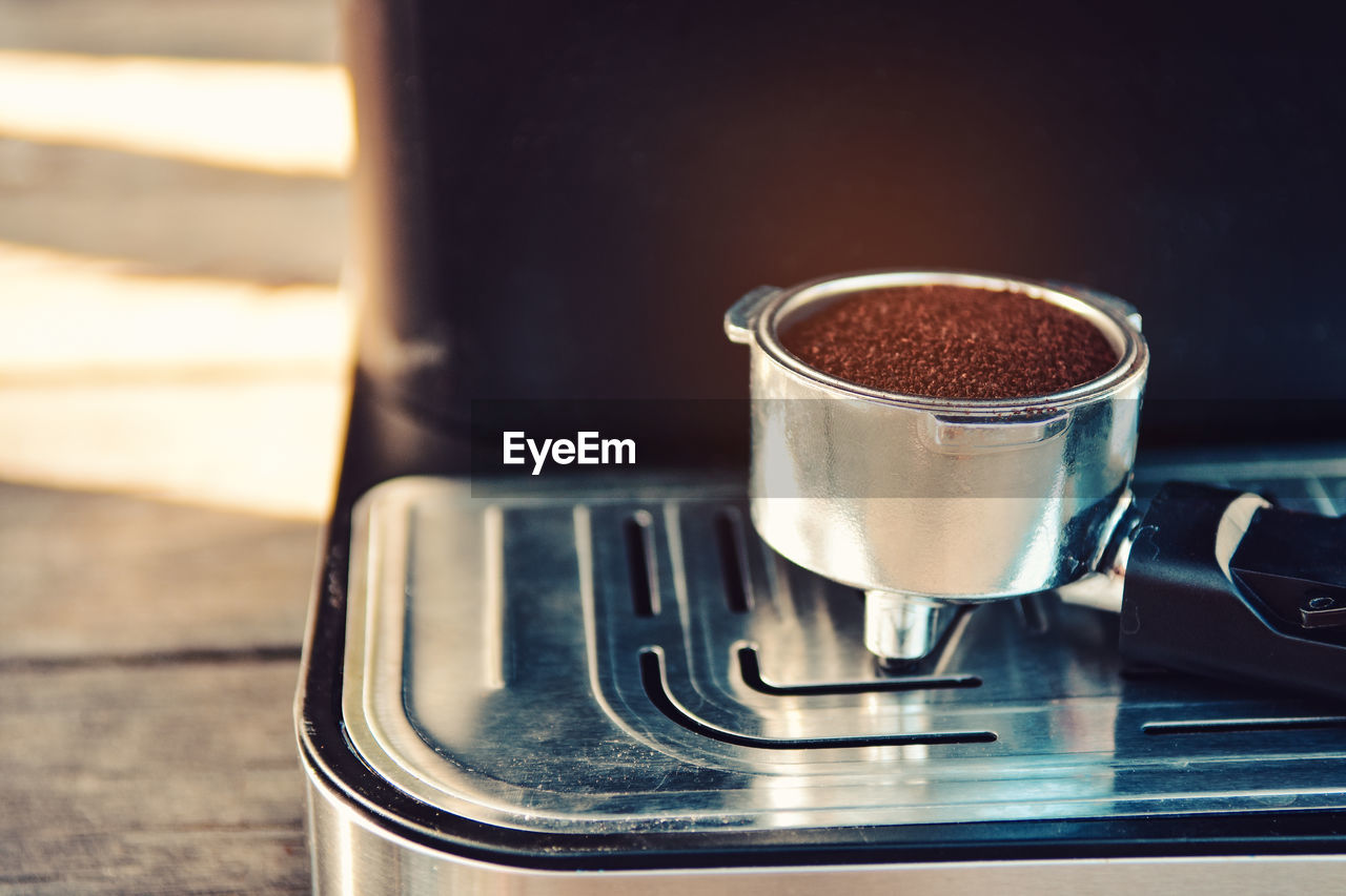 food and drink, appliance, coffee, coffee maker, close-up, still life, coffee - drink, table, metal, focus on foreground, drink, indoors, no people, stove, refreshment, preparation, household equipment, espresso maker, heat - temperature, freshness, steel, caffeine, coffee shop