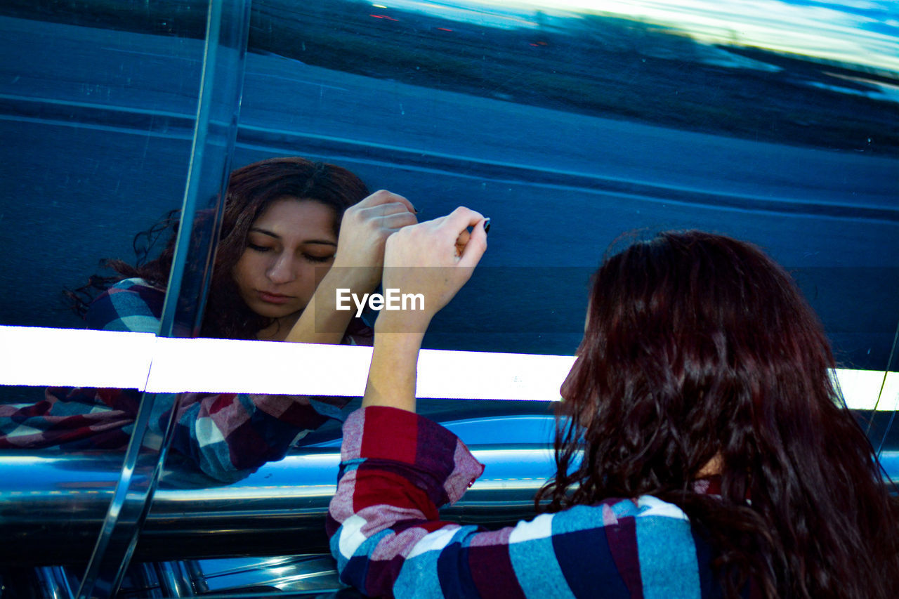 Reflection of young woman on vehicle