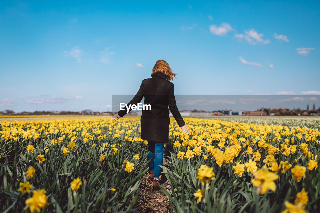 FULL LENGTH OF WOMAN STANDING ON YELLOW FLOWERS