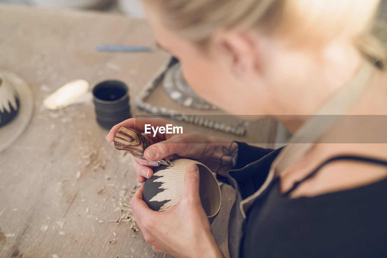 one person, real people, holding, indoors, skill, working, work tool, selective focus, workshop, occupation, human hand, art and craft, hand, craft, concentration, wood - material, high angle view, making, hairstyle