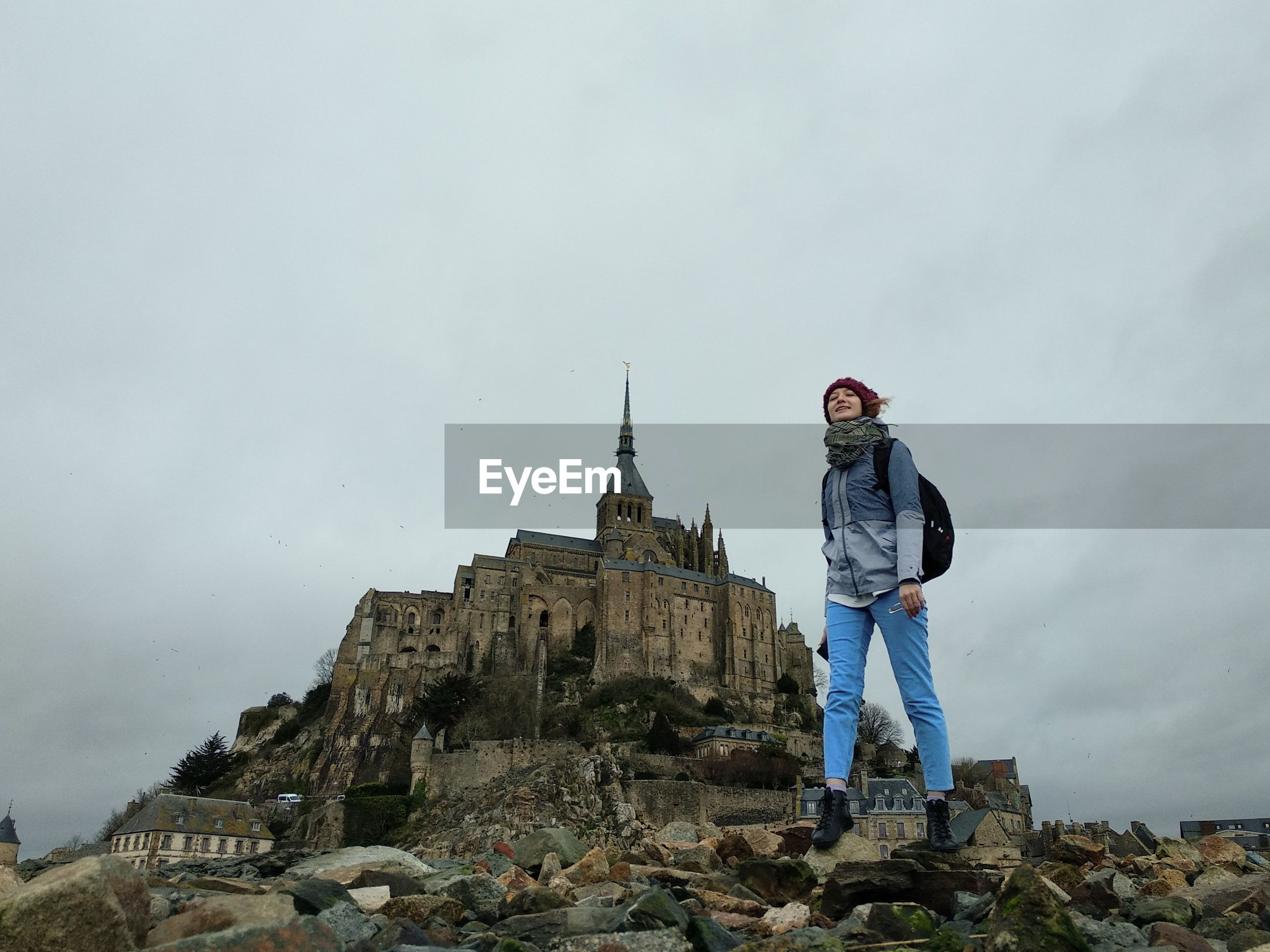 Girl standing on rocks against the mont saint michel
