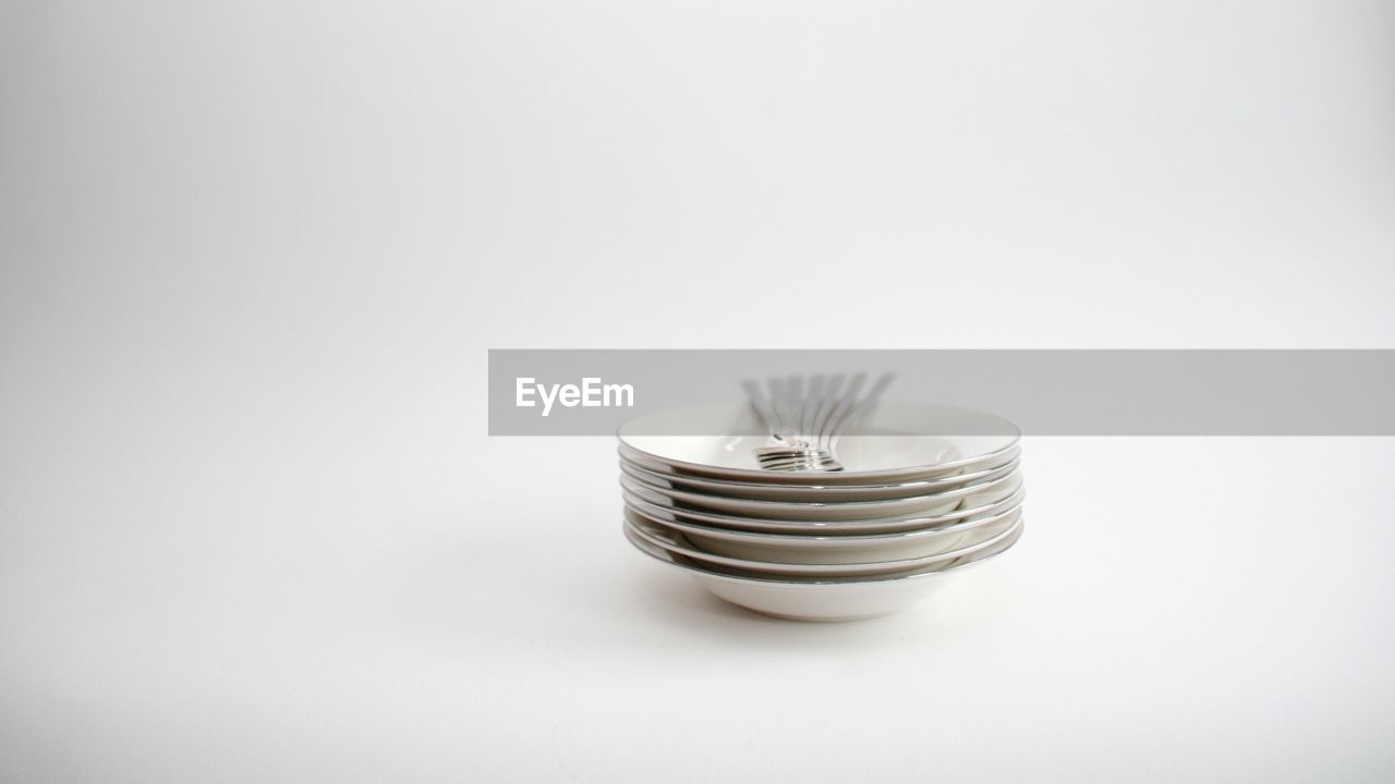 Close-up of forks on plates over white background