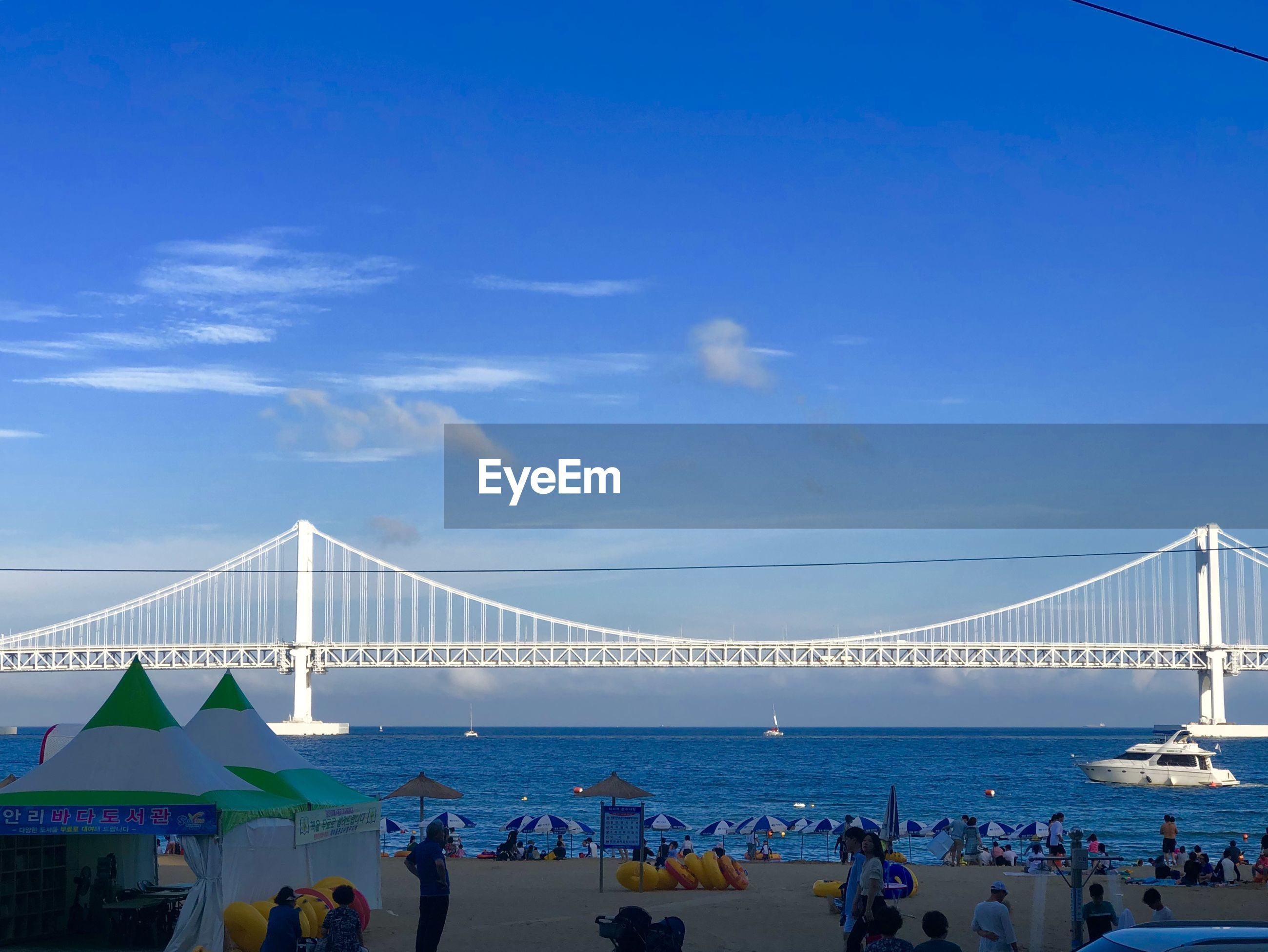 People at beach with suspension bridge over sea in background against blue sky
