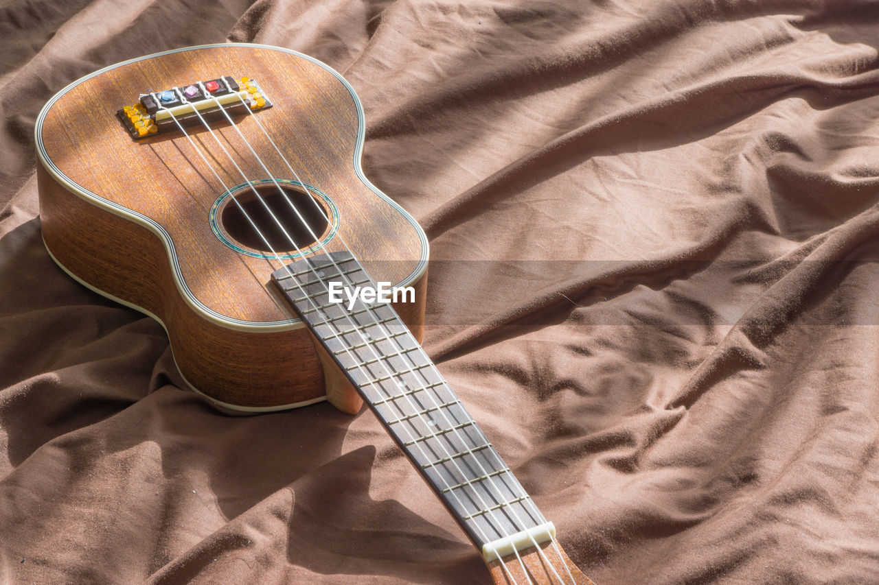 string instrument, guitar, musical instrument, bed, music, high angle view, sheet, indoors, still life, arts culture and entertainment, musical equipment, no people, string, musical instrument string, furniture, textile, acoustic guitar, linen, bedroom, day